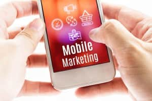 Close up Two hand holding smart phone with Mobile Marketing word and icons, Digital concept.