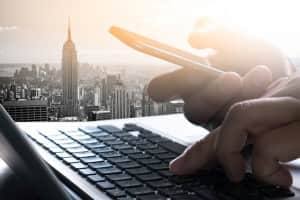 designer  working and smart phone and laptop on wooden desk in office and data with city background