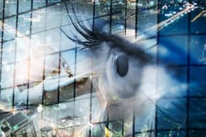 Eye looks to the future business. Woman's eye in the double exposure of a modern city and technology.Eye looks to the future business. Eye women in double exposure with charts and diagrams business.