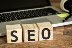 SEO (Search Engine Optimization) written on a wooden cube in front of a laptop