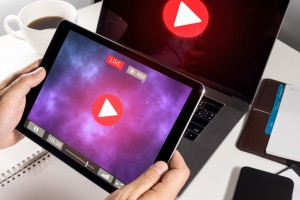 Man Hand Holding Tablet with Live Streaming with Modern laptop computer .Internet social  marketing concept